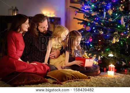 Young Happy Family Of Four Unwrapping Christmas Gifts By A Fireplace