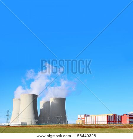 Modern nuclear power plant with fuming cooling towers. Industrial background with space for your text.