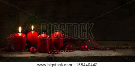 Four red candles two of them burning on the second advent christmas decoration with spruce twigs and baubles on a rustic board dark wooden background with copy space panorama banner or website header selective focus