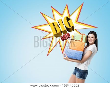 Smiling woman wearing shorts and a T-shirt and holding presents near a blue wall with a big sale poster on it. Mock up