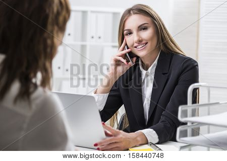 Smiling woman with brown hair is looking at the camera. Her colleague is sitting with her back to the viewer