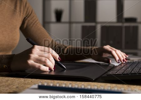 Woman's hands. She has dark red nail polish and is drawing with a stylus on her pad. She is sitting at a dark office. Bookcase is in the background.