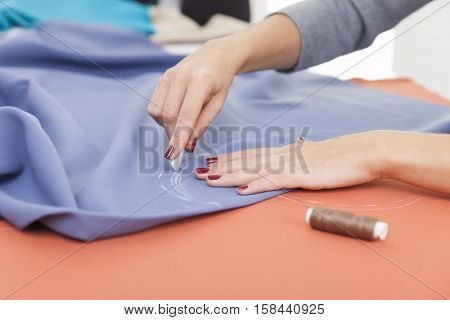Close up of woman's hands drawing a pattern on blue material at her workplace in a tailor shop