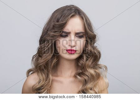 Close up of confused or doubtful woman with long brown hair who is looking down. Concept of mixed feelings