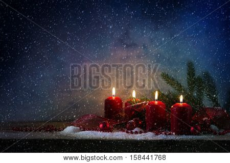 Four red advent candles burning in the snow on a rustic wooden board christmas decoration with fir branches baubles and a gift ribbon against a blue vintage background with plenty of copy space selective soft focus narrow depth of field