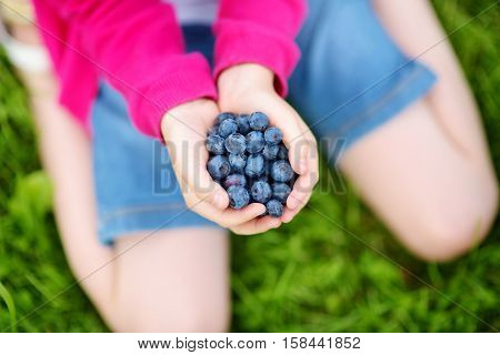 Close-up Of Childs Hands Holding Fresh Blueberries