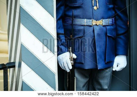 Honor guard man officer in blue military national uniform armed with rifle on post in watchbox