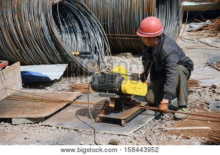 man cutting a steel bar with machine