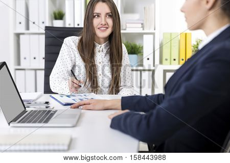 Smiling businesswoman in a polka dot blouse is looking at her colleague who is partly off screen. Mock up