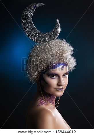Winter portrait of a girl with creative make-up on a dark blue background. Silvery Moon of silver hair in curls. Purple - Gold Makeup.