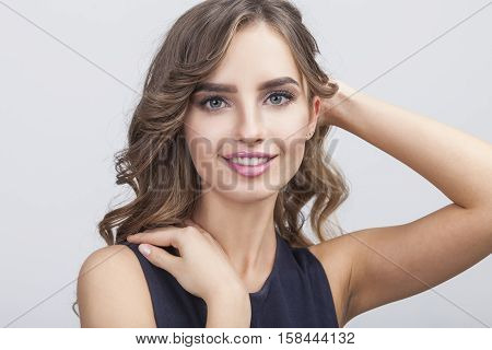 Close up of gorgeous woman with brown wavy hair and big eyes. She is touching her shoulder with one hand and looking at the viewer with tenderness