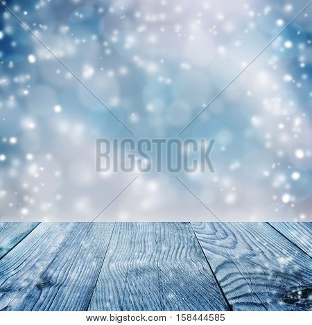 Beautiful blue blurred background of winter and old table. Old boards and falling snow. Christmas. New Year. Winter. Card. Boke.