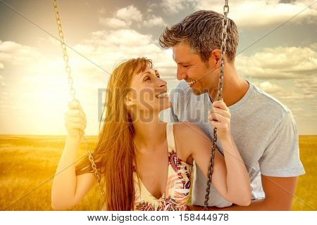 happy lovers swinging with sun behind