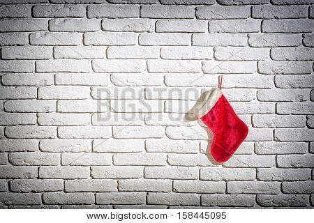 christmas red santa claus stocking at xmas holiday or new year on white brick wall background copy space