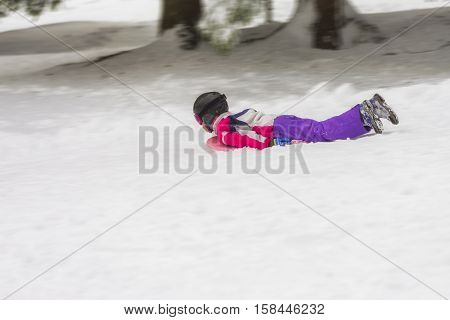Young child (might be boy or girl) outdoors in winter with a toboggan carpet sled board speeding downhill facing away from the viewer