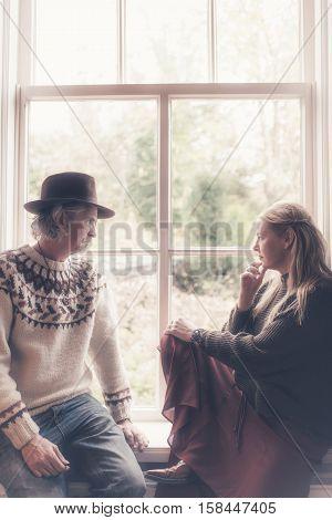 Vintage 1970S Hippie Couple Sitting On Windowsill Looking Outside.