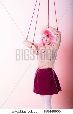 Young woman girl stylized like marionette puppet on string