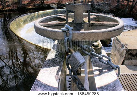 Chained and locked aluminum wheel of a water flow gate on a horse shoe shaped dam.