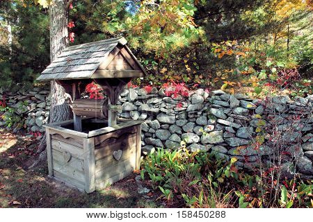 A decorative wooden well sitting next to a stone wall on a sunny autumn day.