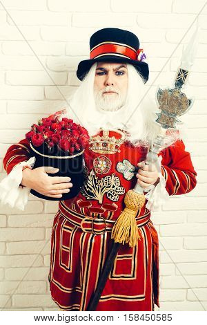 Frowning senior man beefeater yeomen warder or male royal guard bodyguard in red uniform with flowers and spear on white brick wall