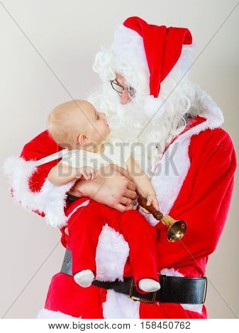 Christmas family holiday concept. Father wearing santa claus hat holding baby in aureole.