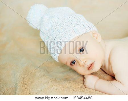 Little Baby Boy In White Hat On Blanket