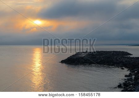 Warm sunlight shines through cloudy foggy mist.  Shadowy derelict boulder pile pier extends into the water and lies in state of disrepair.   Calm daybreak in Eastern most, Atlantic Canada.