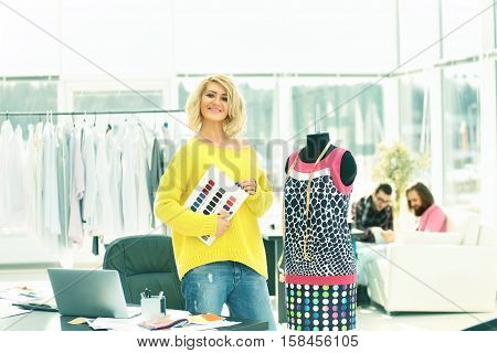 fashion designer near mannequin with the dress on Studio background