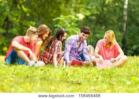 group of students with notebooks in a Park on a Sunny day