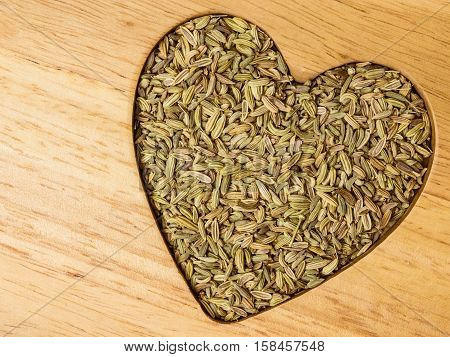 Fennel Dill Seeds Heart Shaped On Wooden Board