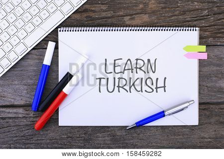 Notebook with LEARN TURKISH Handwritten on wooden background and Modern Computer Keyboard. Top View Composition