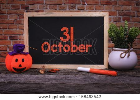 Pumpkin Head Candle and a Chalkboard written 31 October on wooden background