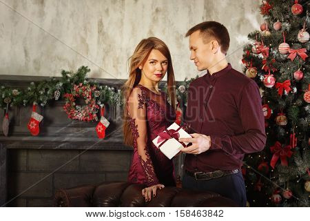 Loving couple and Christmas. Girl gives her boyfriend a Christmas gift. In the background a beautiful Christmas tree.