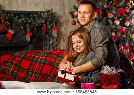 Loving couple and Christmas. Girl hugging boyfriend. She is holding a Christmas gift. In the background a beautiful Christmas tree. Home comfort