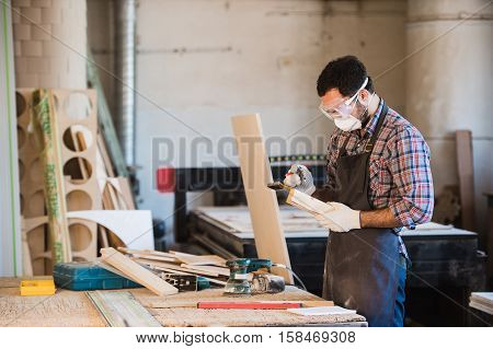 Horizontal view of professionally dressed carpenter varnishing a board.