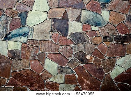 Old stone masonry wall texture background, with irregular pattern, colorful and cracked, toned