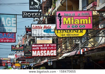 PATTAYA THAILAND - 22 NOV 2016: Massage and other multicolored signs on the street of Beach Road. The average price for one hour of oil massage is 300 baht around 10 dollars.