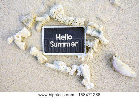 Hello Summer text written on chalkboard on beach