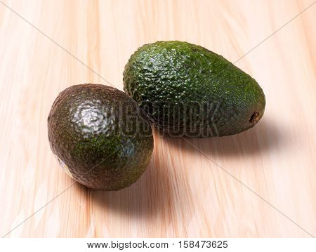 Two Green Avocados on wooden board table