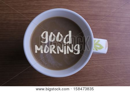 Message good morning coffee cup and business strategy on wooden table
