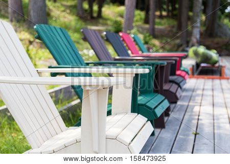 a row of Muskoka chairs sitting on the dock facing out to the lake inviting you to come sit for a while