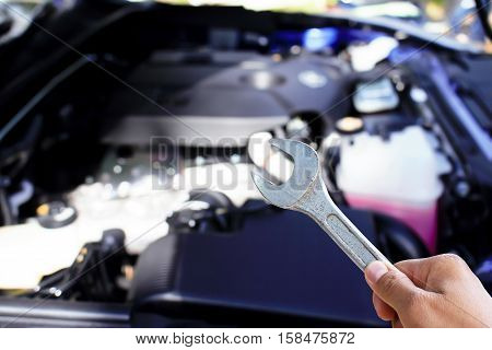 Hand with wrench checking car engine new