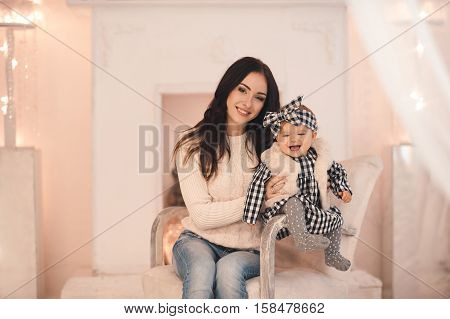 Smiling young mother holding her little baby girl under 1 year old sitting in armchair over white fireplace in room. Looking at camera. Wearing casual style clothes. Christmas time. Winter season.