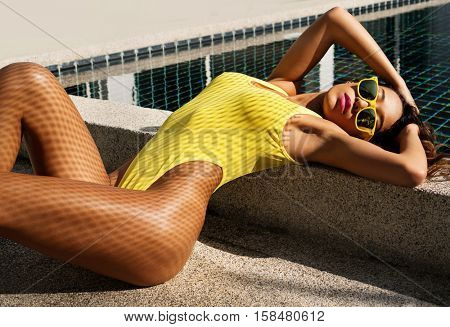 Sexy woman with fit body in fashionable elegant yellow bikini swimsuit and sunglasses lying down and posing with fishnet shadow pattern on her body beside the swimming pool. Summer relax concept