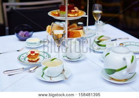Beautiful table setting with selection of sandwiches fancy cakes tea and champagne served for the ceremony of afternoon tea