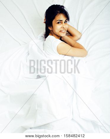 young pretty tann woman in bed among white sheets having fun, trying to sleep, fooling around, lifestyle concept at home