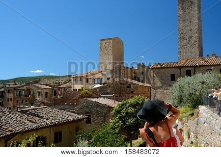 San Gimignano Italy - September 6 2016: Unidentified woman in black hat taking picture of San Gimignano city in Tuscany Italy. Unidentified people visible.