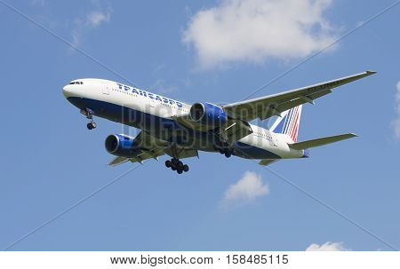 SAINT PETERSBURG, RUSSIA - JUNE 29, 2015: The aircraft of Transaero Airlines Boeing 777-200/ER on approach to Pulkovo airport