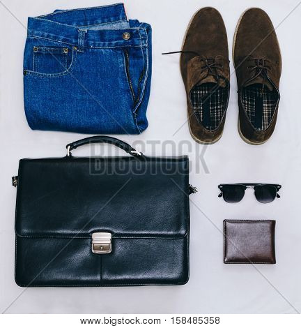 Outfit of business man with vintage blue jeans, black briefcase, brown suede shoes, clubmaster sunglasses and purse on the gray background