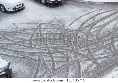 Top view of the traces of car tires on wet snow after turning cars during sleet